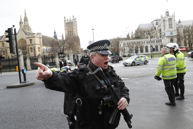 This March, a police officer wards away onlookers after the attack outside the Houses of Parliament (AFP)
